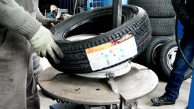 Mechanic Using Tire Mounting Tool Machine, Car mechanic mounting tire on alloy wheel, Mechanic Guy In Dirty Work Wear. Kherson, Ukraine 20 October 2016: Tire stock footage
