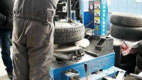 Mechanic using tire mounting tool machine. Car repair garage. car maintenance, Seasonal tire change period. Kherson, Ukraine 20 October 2016: Tire service stock video footage