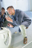 Mechanic using tube sealant Royalty Free Stock Images
