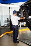 Mechanic Using Wheel Alignment Machine On Car. Full length rear view of mechanic using wheel alignment machine on car in garage Stock Images