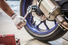 Mechanic using a wrench and socket on the engine of a motorcycle. Selective focus Royalty Free Stock Photography