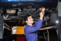 Mechanic Using Wrench Underneath Lifted Car. Male mechanic using wrench underneath lifted car at auto repair shop Stock Images
