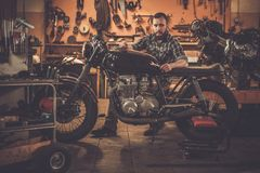 Mechanic and vintage style cafe-racer motorcycle Stock Photos