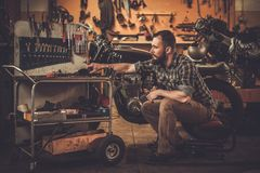 Mechanic and vintage style cafe-racer motorcycle Royalty Free Stock Photography