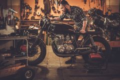 Mechanic and vintage style cafe-racer motorcycle Stock Image