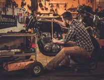Mechanic and vintage style cafe-racer motorcycle Royalty Free Stock Image