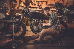 Mechanic and vintage style cafe-racer motorcycle. Mechanic building vintage style cafe-racer motorcycle in custom garage royalty free stock photos