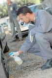 Mechanic washing customer's car wheels Royalty Free Stock Photos