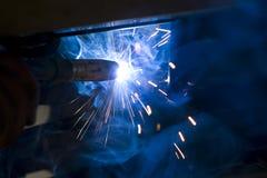 Mechanic welding under car Stock Photos