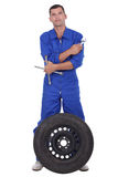Mechanic with wheel. Mechanic stood with a wheel royalty free stock photos