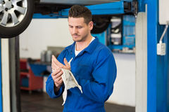 Mechanic wiping hands with rag. At the repair garage Stock Photo