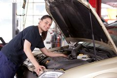 Mechanic Woman. Portrait of a happy mechanic woman working on a car in an auto repair shop royalty free stock images