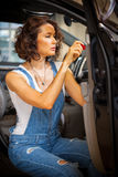 Mechanic woman in a blue overalls repair with a screwdriver the Stock Image