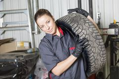 Mechanic woman working on car in his shop Stock Photos