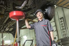 Mechanic woman working on car in his shop Stock Photo