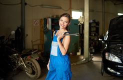 Mechanic woman with smile in working clothes in repair garage royalty free stock photography