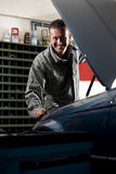 Mechanic at work. Smiling mechanic controlling car engine royalty free stock photo