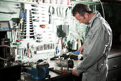 Mechanic at work. Close-up of a smiling mechanic inside his auto repair shop Stock Photography