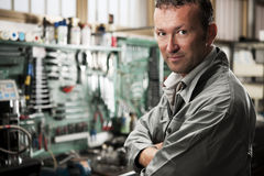 Mechanic at work. Close-up of a smiling mechanic inside his auto repair shop Royalty Free Stock Photography