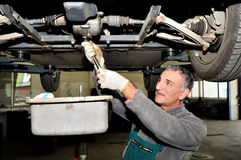 Mechanic at work. Mechanic changing engine oil under the car stock images