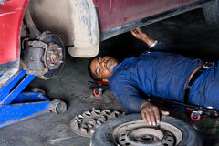 Mechanic at work. An indian mechanic working on a broken down vehicle royalty free stock photos