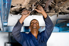 Mechanic at work. African american mechanic working on vehicle wheel alignment stock image