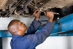 Mechanic at work. African mechanic working on vehicle wheel alignment stock photos