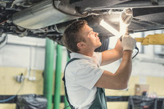 Mechanic at work. Young mechanic in a garage royalty free stock photos