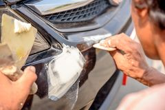 Mechanic worker repairman fixing scratched on car body and prepa. Ring for painting Royalty Free Stock Image