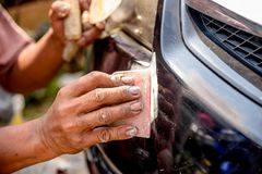Mechanic worker repairman fixing scratched on car body and prepa. Ring for painting Stock Photos