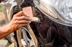 Mechanic worker repairman fixing scratched on car body and prepa. Ring for painting Stock Images