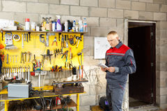 Mechanic worker studying his instructions Royalty Free Stock Images
