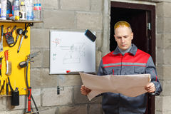 Mechanic worker studying his instructions Royalty Free Stock Photo