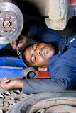 Mechanic working. A mechanic working under a car Stock Photography