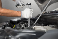 Mechanic working in auto repair garage. Car maintenance.  Royalty Free Stock Images