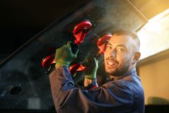 Mechanic working in auto repair shop. Mechanic changing glass workshop.Looking at camera Stock Photography