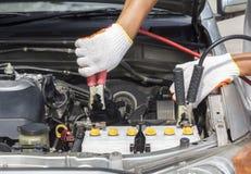 Mechanic working in auto repair shop. Mechanic using jumper cables in auto repair shop Stock Photos