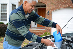 Mechanic Working On Car. Mechanic working on a car in his driveway royalty free stock image