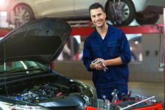 Car mechanic in auto repair shop. Mechanic working on car in auto repair shop royalty free stock images