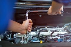 Mechanic working on car engine in auto repair shop royalty free stock photos