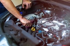 Mechanic working on car engine in auto repair shop. Hands of mechanic working on car engine in auto repair shop stock photo