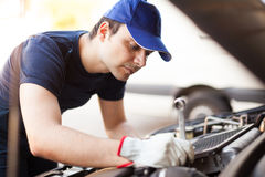 Mechanic working on a car engine Royalty Free Stock Photos