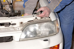 Mechanic working on a car headlight Royalty Free Stock Image