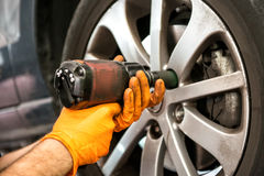 Mechanic working on a car wheel. Tightening or loosening the bolts on the hub and rim with an electric power tool, close up view of his hands royalty free stock image