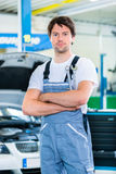 Mechanic working in car workshop Royalty Free Stock Image