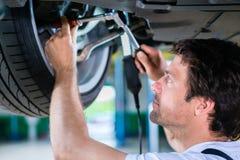 Mechanic working in car workshop on wheel Royalty Free Stock Photo