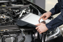 Mechanic working at the computer. Royalty Free Stock Images