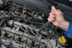 Auto Mechanic. Mechanic is working on engine in car repair shop Stock Image