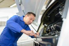 Mechanic working on front motor caravan. Mechanic working on front of motor caravan Stock Photography