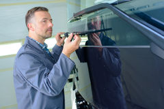 Mechanic working on front vehicle Stock Images